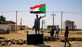File photo: A Sudanese protester holds a national flag, demanding that the country's Transitional Military Council hand over power to civilians, in Khartoum, Sudan June 5, 2019.