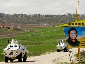 UNIFIL armored vehicles drive past a billboard bearing a portrait of a killed Hezbollah fighter, near the village of Marjayoun, in southern Lebanon, near the Lebanon-Israel border. March 15, 2014