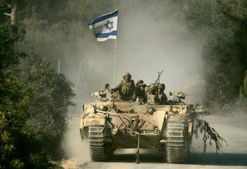 Israeli soldiers ride a tank returning from southern Lebanon after a UN-imposed cease-fire went into effect to end a month of violence that killed more than 900 people. Aug. 14, 2006
