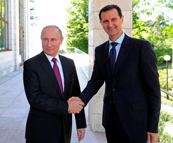 Russian President Vladimir Putin, shakes hands with Syrian President Bashar Assad during a meeting in Sochi, Russia, May 17, 2018.