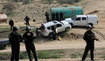 Israeli policemen stand guard next to a vehicle that rammed into a group of policemen, killing one, in the Bedouin village of Umm al-Hiran in the Negev in southern Israel, Jan. 18, 2017.