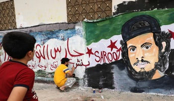 A child watches as a local artist works on a mural painting showing the late Syrian rebel fighter Abdel-Basset al-Sarout in the town of Binnish in the northern Idlib province on June 8, 2019.
