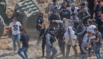 Israeli border police arrest protesters and activists blocking Israeli army bulldozer operating at the West Bank Bedouin community of Khan al-Ahmar, Sept. 14, 2018.