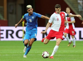 Poland's Robert Lewandowski, right, duels for the ball with Israel's Yonatan Cohen, left, at the Narodowy stadium in Warsaw, Poland, June 10, 2019