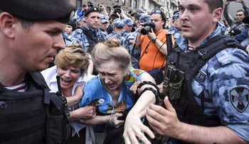 Russian police officers detain protesters during a march to protest against the alleged impunity of law enforcement agencies in central Moscow on June 12, 2019