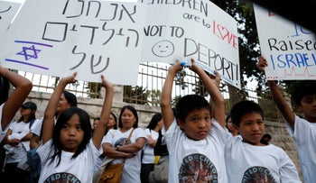 """Filipino mothers with their children demonstrate opposite the prime minister's residence in Jerusalem. Sign on the left reads """"We are the children of Israel."""" On Tuesday, June 11, 2019."""