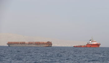 A tugboat moves cargo towards the Strait of Hormuz off the coast of Oman, July 20, 2018.