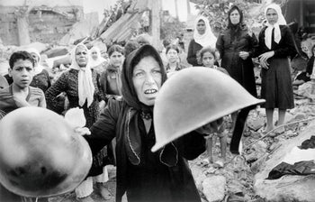 A Palestinian woman brandishes helmets she says were worn by the perpetrators of the Sabra and Shatila massacre during a memorial service in Beirut for its victims. Sept. 27, 1982