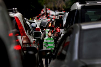 A Syrian refugee girl begs for money in traffic, in Beirut, Lebanon. Studies show more than 1,500 children living or working on Lebanon's streets, nearly three-quarters of them Syrian. Feb. 10, 2016