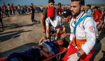 Palestinian evacuate a wounded demonstrator near Bureij in the central Gaza Strip on June 14, 2019.