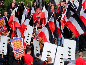 """Supporters of the German neo-Nazi party """"Die Rechte"""" carry the Imperial War Flag used by German armed forces between 1867 and 1945 and posters announcing """"Israel is our misfortune."""" May Day rally, Duisburg. May 1, 2019"""