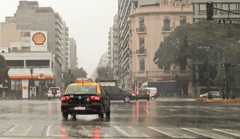 Cars drive past blacked-out traffic signals at the 9 de Julio avenue during a power cut in Buenos Aires on June 16, 2019