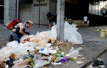 People check a garbage pile for food, in Caracas, Venezuela, March 18, 2019