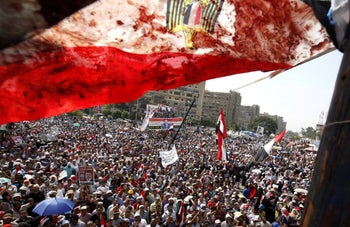 File photo: An Egyptian flag stained with blood flutters over members of the Muslim Brotherhood during a protest in Cairo in 2013.