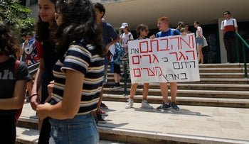 Israeli students hold a sign quoting a biblical verse, 'you shall love [the stranger] as yourself, for you were strangers in the land of Egypt,' in Tel Aviv on June 17, 2019.