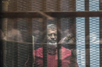 Morsi stands behind the bars during his trial in Cairo at the police academy, April 23, 2016.