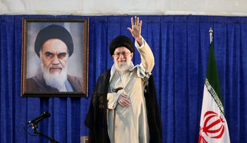In this picture released by the official website of the office of the Iranian supreme leader, Supreme Leader Ayatollah Ali Khamenei waves to the crowd while attending a ceremony marking 30th death anniversary of the late revolutionary founder Ayatollah Khomeini, shown in the poster at rear, at his mausoleum just outside Tehran, Iran, Tuesday, June 4, 2019
