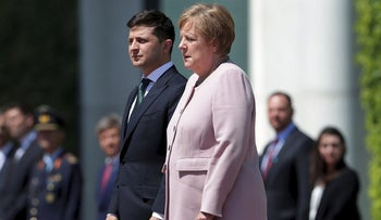 German Chancellor Angela Merkel, right, trembles strong as she and Ukraine's President Volodymyr Zelenskiy, left, attend the national anthems as part of a military welcome ceremony in Berlin, Germany, Tuesday, June 18, 2019