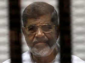 Mursi is seen behind bars during his trial at a court in Cairo May 8, 2014.