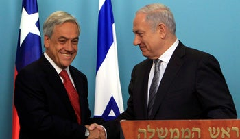 Pinera shakes hands with Netanyahu on his first diplomatic visit to Israel, March 6, 2011.