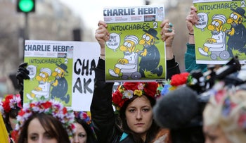 In a file photo taken on January 11, 2015 Femen activists hold Charlie Hebdo front pages during a Unity rally in Paris.