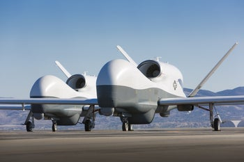 Two MQ-4C Triton unmanned aerial vehicles are seen on the tarmac at a Northrop Grumman test facility in Palmdale, Calif