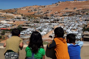 Lebanese children look from the rooftop of their home at a Syrian camp in Arsal, Lebanon, June 16, 2019.
