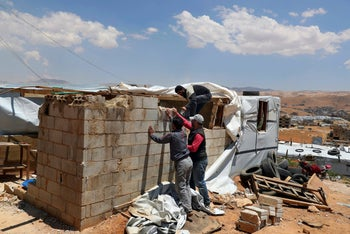 Syrian refugees demolish a concrete wall built inside their tent at a refugee camp in Arsal, Lebanon, June 16, 2019.