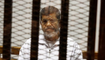 FILE Photo: Egypt's ousted Islamist President Mohammed Morsi sits in a defendant cage in the Police Academy courthouse in Cairo, Egypt, May 8, 2014.