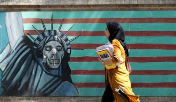 A woman walks past a mural painting along the wall of the former U.S. embassy in Tehran, June 22, 2019