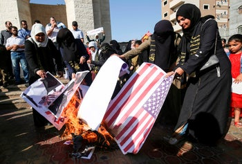 Palestinian female supporters of the Islamic Jihad burn posters of US President Donald Trump and Israeli Prime Minister Benjamin Netanyahu during a protest against the Bahrain economic workshop in the southern Gaza Strip town of Rafah on June 18, 2019