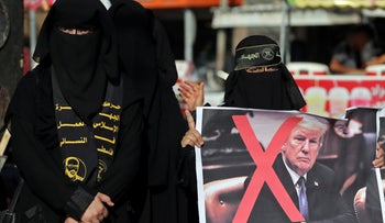 File photo: A Palestinian woman holds a crossed-out poster depicting U.S. President Donald Trump during a protest against Bahrain's workshop for U.S. peace plan, in the southern Gaza Strip June 18, 2019