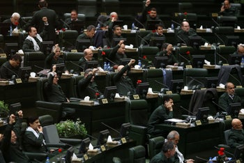 """Wearing the uniform of the Revolutionary Guards, Iranian lawmakers chant """"Death to America"""" during an open session of parliament in Tehran, April 9, 2019."""