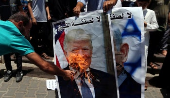 A Palestinian demonstrator burning a poster depicting U.S. President Donald Trump during a protest against Bahrain's workshop for U.S. Middle East peace plan, in the southern Gaza Strip, June 25, 2019.