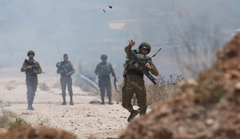 Israeli border police use teargas to disperse Palestinian protesters during a rally against the American-led Mideast peace conference, near the settlement of Beit El, at the outskirts of the West Bank city of Ramallah Tuesday, June 25, 2019