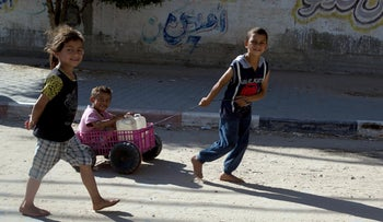Palestinian children push a wagon with containers of drinkable water to their homes in Gaza City, May 12, 2019.