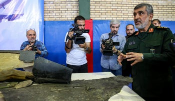 General Amir Ali Hajizadeh (R), Iran's Head of the Revolutionary Guard's aerospace division, speaks to media next to debris from a downed US drone reportedly recovered within Iran's territorial waters and put on display in the capital Tehran, June 21, 2019