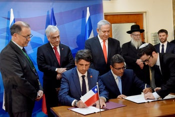 Netanyahu and Pinera observe government officials signing bilateral agreements in Jerusalem, June 26, 2019.