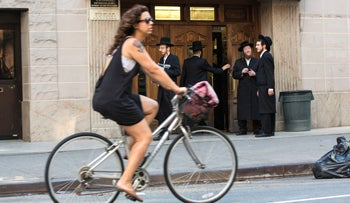 A cyclist passes Hasidic Jews outside of a synagogue on Bedford Avenue in the Brooklyn borough of New York, Aug. 13, 2013.