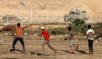 Palestinian protesters run during clashes with Israeli forces following a demonstration along the fence east of Khan Yunis in the southern Gaza strip, June 26, 2019.