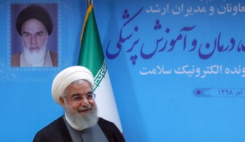 Rohani under a portrait of the late founder of the Islamic republic Ayatollah Ruhollah Khomeini in Tehran, June 25, 2019