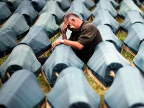 A father cries beside the coffin of his son, one of 534 newly identified Bosnian Muslim victims out of 8,000 murdered by Bosnian Serb forces in the 1995 Srebrenica massacre, before a mass burial in Potocari. July 10, 2009