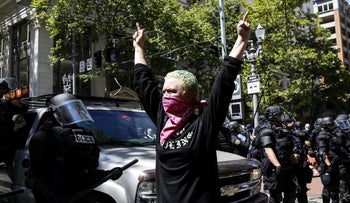 An unidentified Rose City Antifa member flicks off to the police during a demonstration between the left and right at Pioneer Courthouse Square on June 29, 2019 in Portland, Oregon