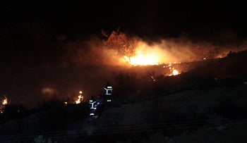 Fire on a hillside that officials said was caused by a suspected Russian missile that exploded overnight in Turkish Cyprus, during an Israeli aerial raid in Syria, July 1, 2019.