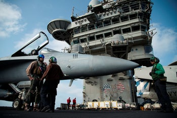 A pilot speaks to a crew member by an F/A-18 fighter jet on the deck of the USS Abraham Lincoln aircraft carrier, deployed to the Middle East to counter the threat of Iran, in the Arabian Sea. June 3, 2019