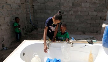 File photo: Libyan children displaced from the town of Tawergha fill containers with water at a displaced camp in Benghazi, Libya, June 19, 2019