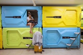 A woman is sitting in a cubicle at the Capsule Inn.