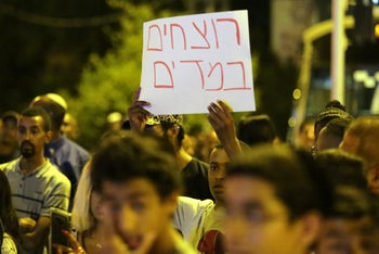 At a demonstration against the shooting of Teka, a protester holds a placard reading 'Murderers in uniform' in Haifa, July 2, 2019.
