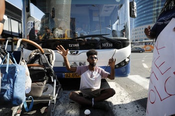 A protester sits in the middle of traffic in Tel Aviv, July 2, 2019