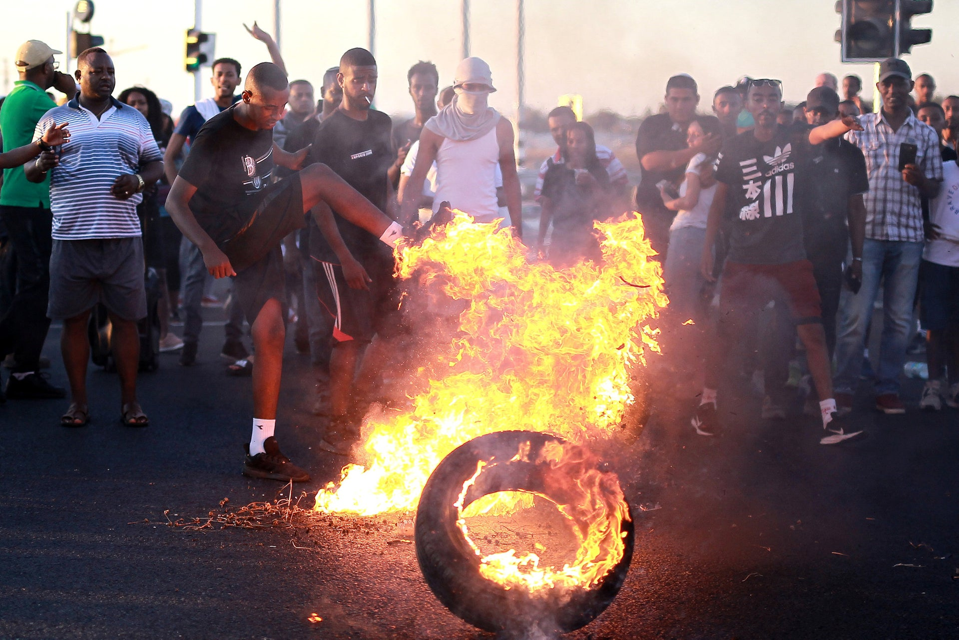 Protesters are burning a tire, as part of a the Ethiopian Israeli protest taking place across the country.